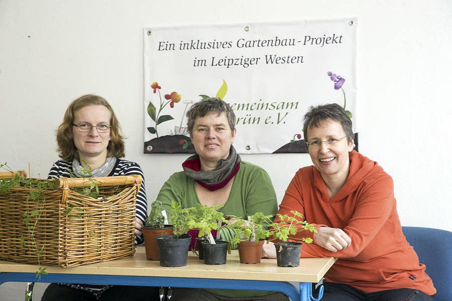 Stephanie, Silke und Sabine sitzen nebeneinander an einem Tisch. Auf dem Tisch befinden sich Pflanzen. Im Hintergrund hängt das Vereinsbanner.