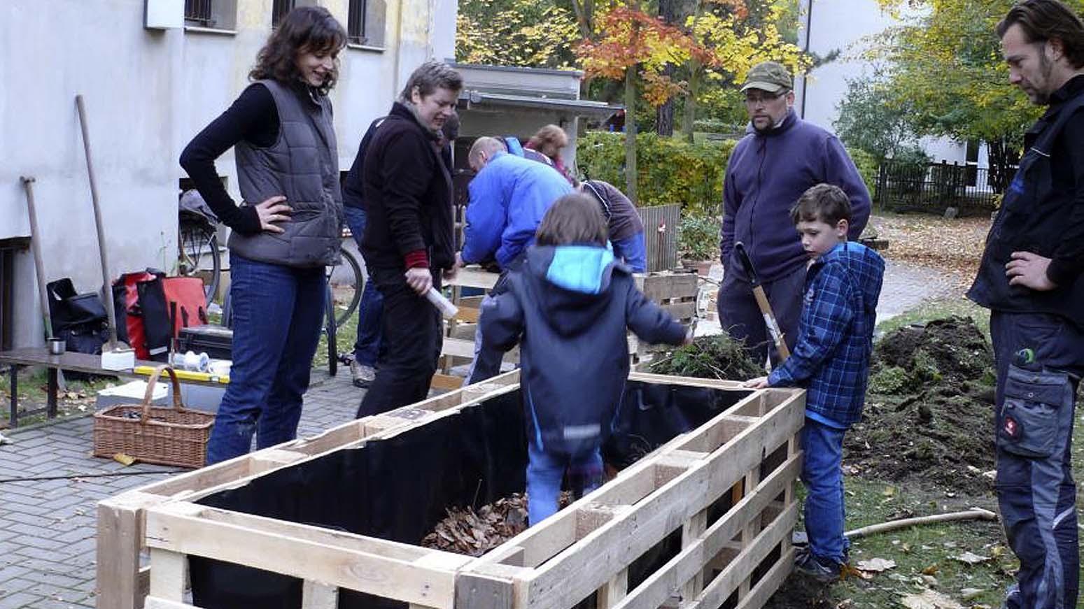 Männer, Frauen, Kinder stehen um ein unfertiges Hochbeet aus Europaletten herum. Ein Kind tritt den Mulch im Hochbeet fest.
