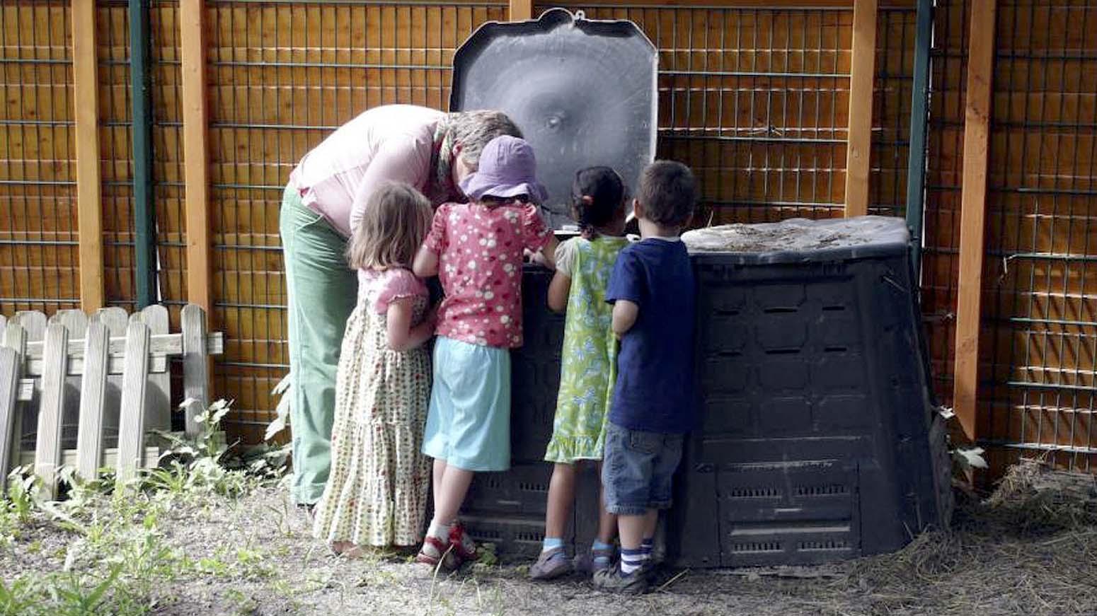 Eine Frau beugt sich mit drei Kindern über eine schwarze Komposttonne.