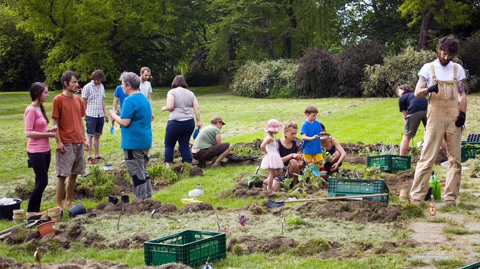 Männer, Frauen und Kinder legen auf einer Parkwiese Beete an.