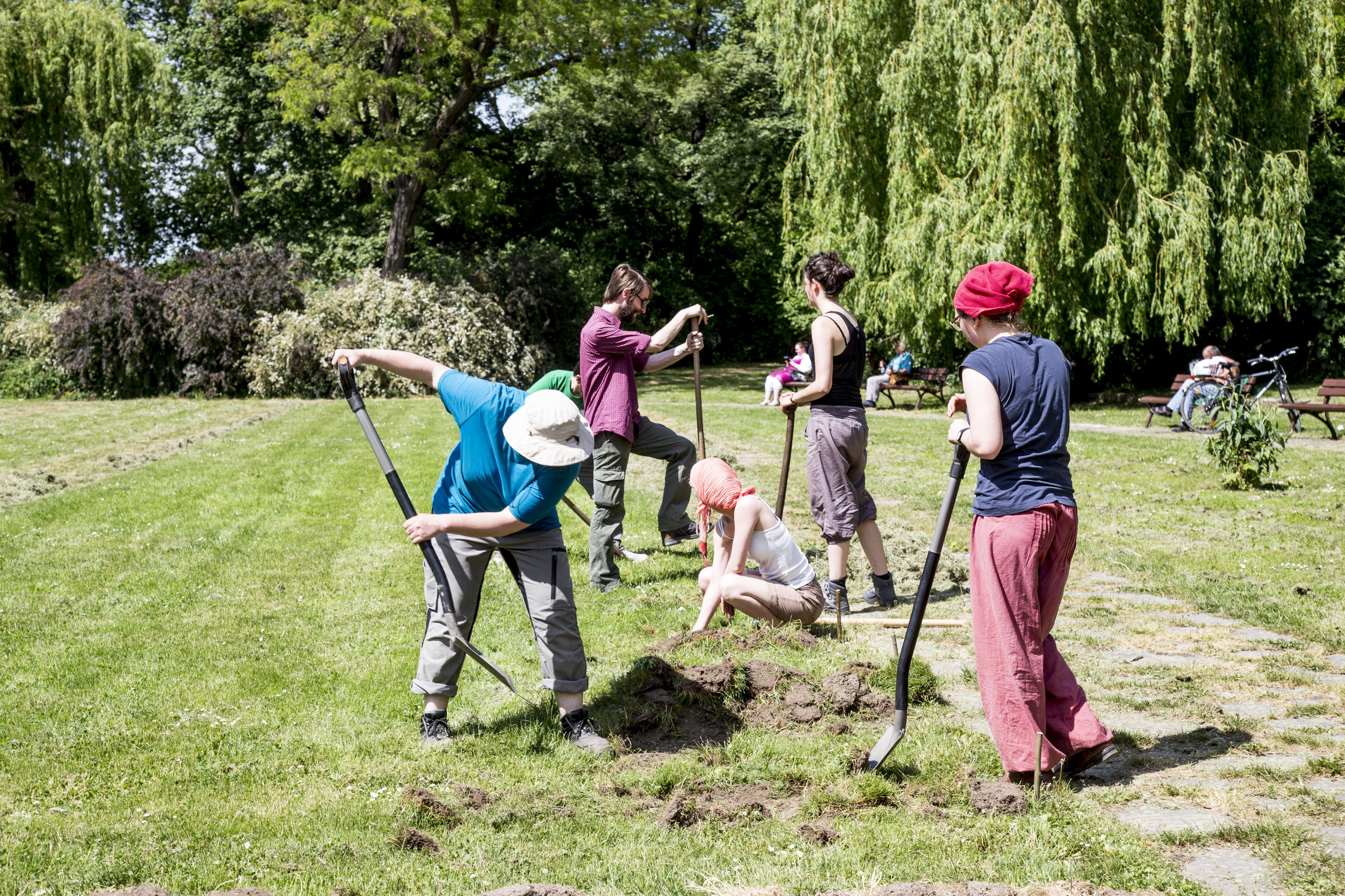 Frauen bei der Gartenarbeit. Sie legen mit Schaufeln erste Beete an.