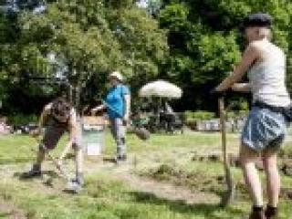 Drei Frauen graben ein Stück Wiese um für ein neues Beet