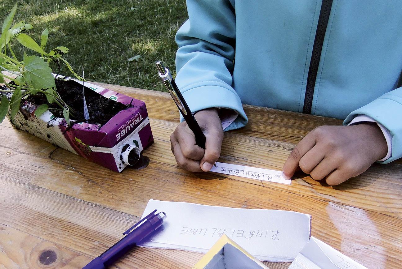 Kind beschriftet am Holzgartentisch eine Pflanzschale aus einem alten Milchkarton.