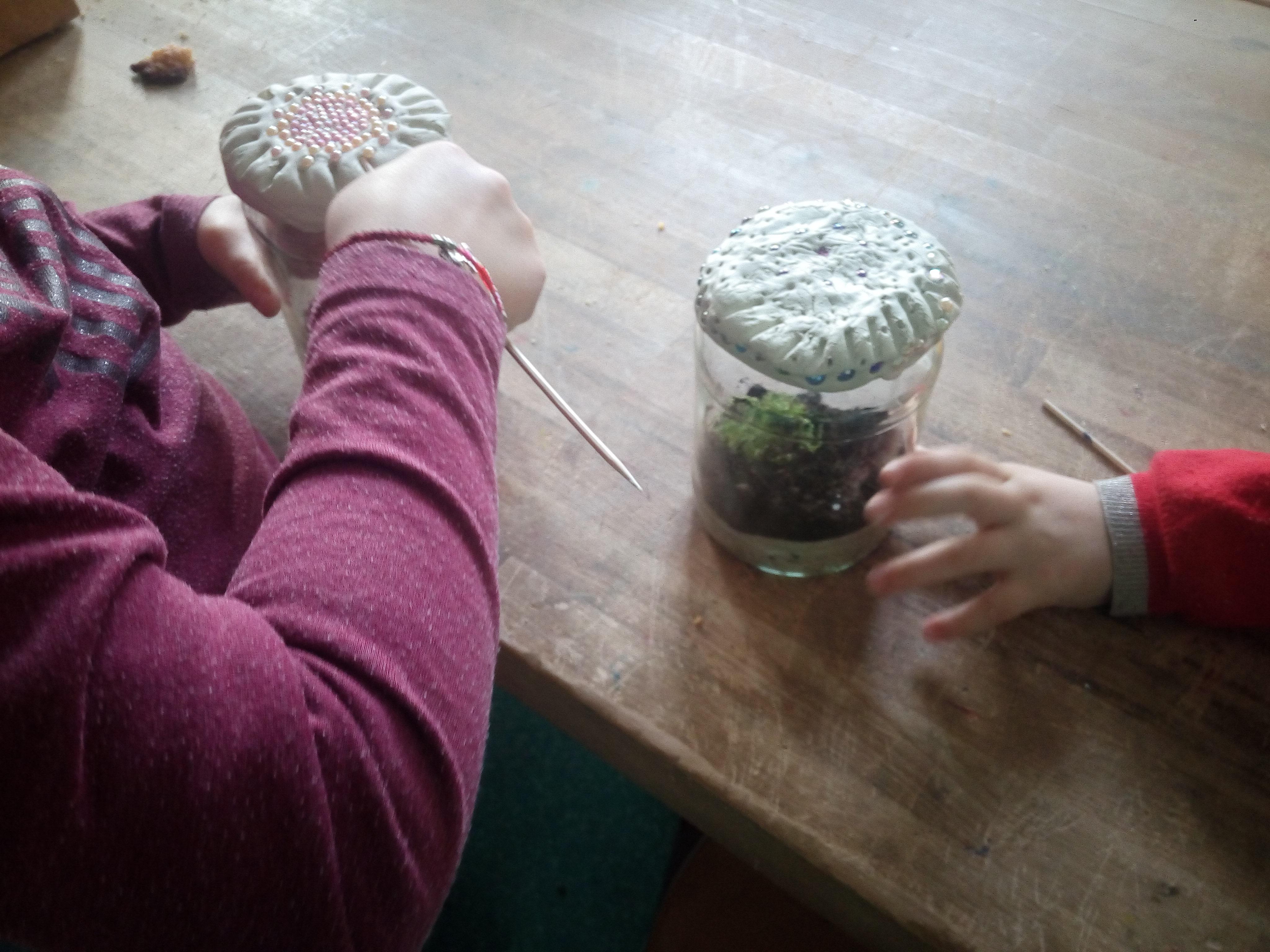 Kinderhände verzieren Deckel von Marmeladengläsern mit Perlenschmuck