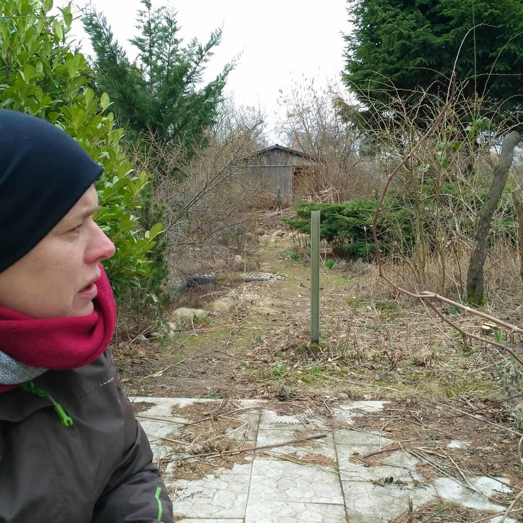 Silke blickt auf die verwilderte, triste, winterliche Gartenfläche