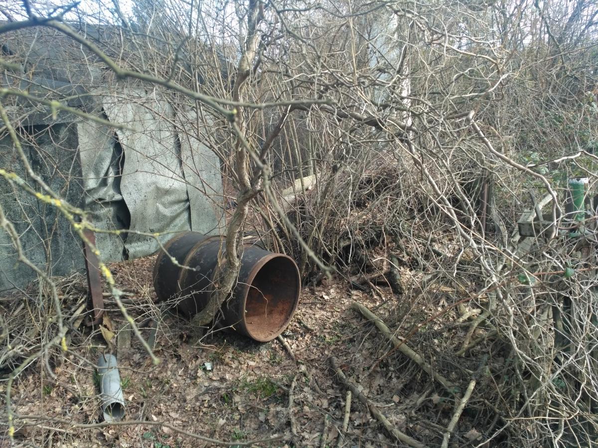 Alte, umgefallene Tonne auf einem verwilderten Grundstück, Stimmung wintertrist