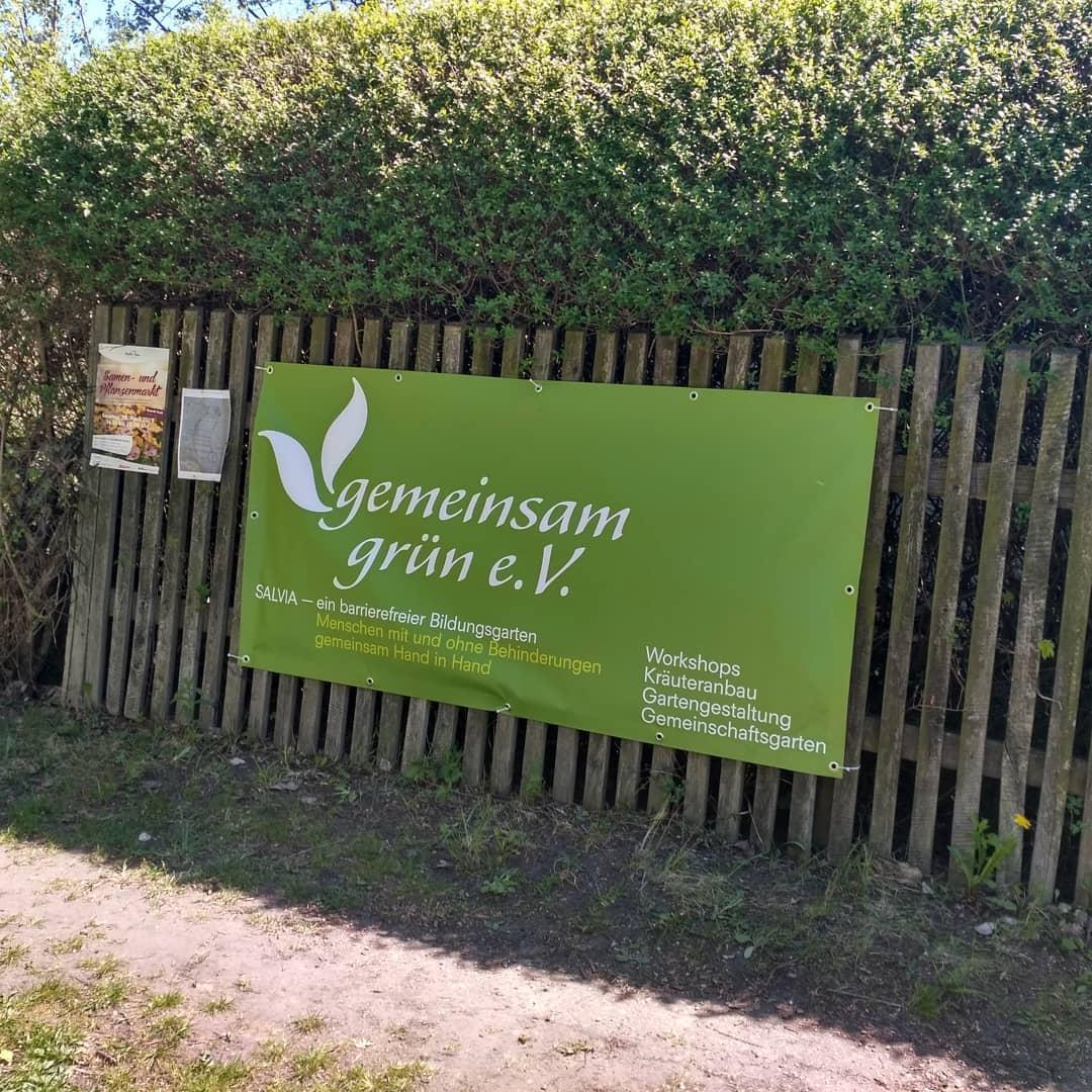 Das große, grüne Banner mit unserem Vereinslogo hängt an unserem Gartenzaun aus alten, verwitterten Holzlatten